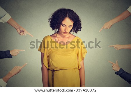 Concept of accusation guilty person girl. Sad embarrassed upset woman looking down many fingers pointing at her back isolated on grey office wall background. Human face expression emotion feeling - stock photo