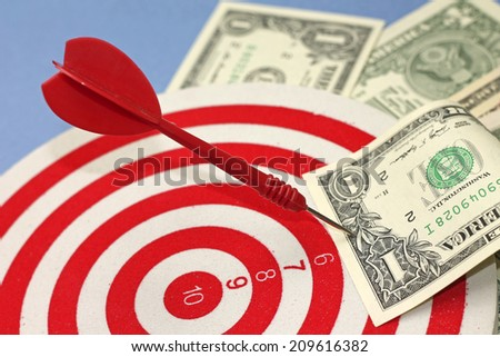 Concept of achieving financial independence - darts and dollars - stock photo