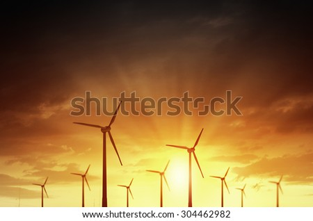 Concept of alternative electricity power with windmills on sunset background