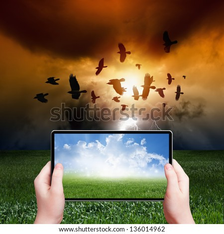 Concept of augmented reality - abstract tablet pc in hands, sunny weather, stormy weather, flock of flying ravens, crows in dark sky with lightning