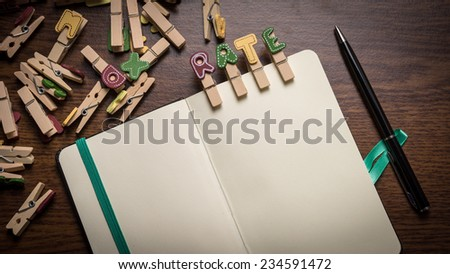 Concept of banking terms - Rate word on clothes peg stick to notepad with pen on the side on wooden floor with room for text - stock photo