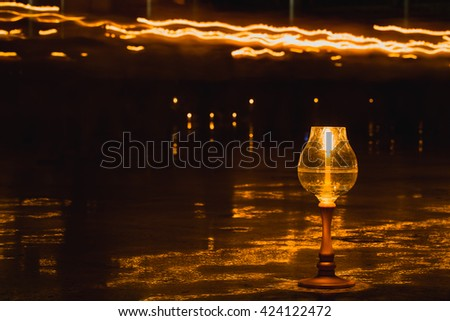 Concept of Buddha candle. In the dark night. The light of a small candle. He also enlightens visitors. Mind the dark. 1 million candlepower, it may not be a shining light for them. - stock photo