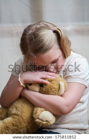 concept of bullying in the home, a young girl sits alone with her arms hugging her teddy bear - stock photo