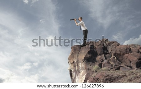 Concept of business exploration with businessman in a mountain - stock photo
