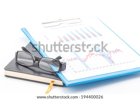 Concept of business graph, glasses on clipboard and notebook. - stock photo