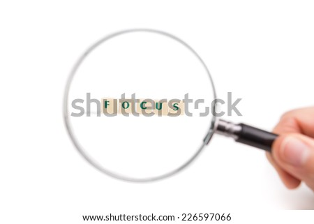 Concept of business idea focus. Magnifying glass in hand on the letters. - stock photo