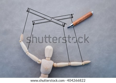concept of business manipulating with wooden figure and drawing on grey background - stock photo