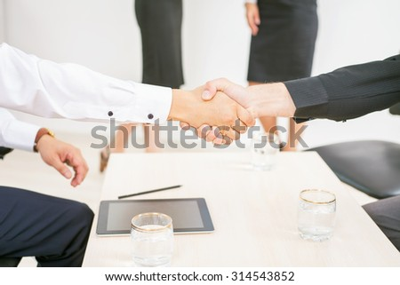 concept of business success - two men shaking hands and there are a two business woman at white background for any text and copy space