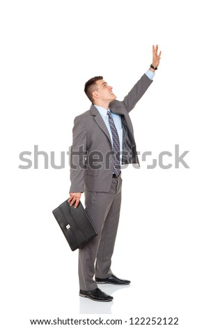 concept of businessman get something with hand take upwards, grab form above, raised up arm point palm finger, business man hold brief case press virtual button, full length isolated white background