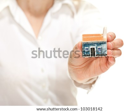 Concept of buying a house: female hand reaching out little house model to you