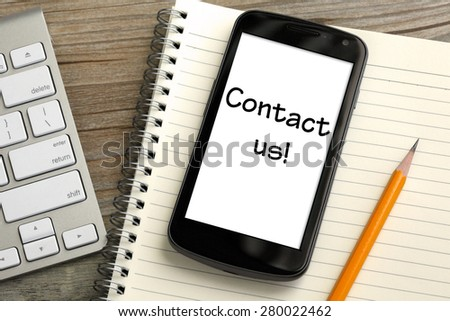 concept of Call Us now, with mobile phone and desk background - stock photo