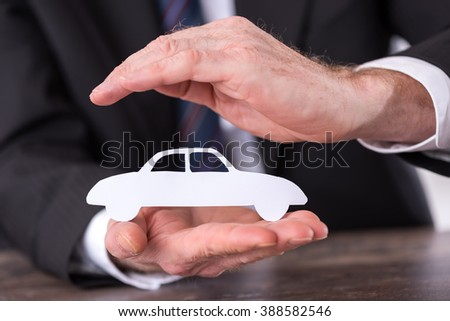 Concept of car insurance with hand over a car - stock photo