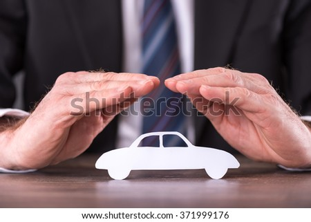 Concept of car insurance with hands over a car - stock photo