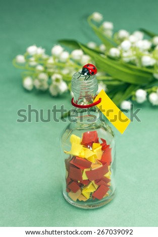 Concept of childhood memories. Bottle with colorful papers, on green backdrop - stock photo