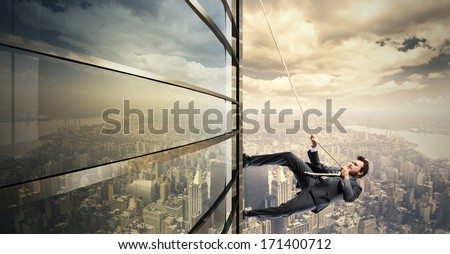 Concept of Climb to the success with climbing businessman - stock photo