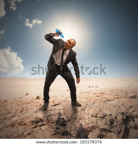 Concept of crisis with businessman with empty bottle in the desert - stock photo