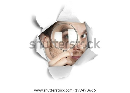 Concept of curiosity with businessman looking through a paper hole - stock photo