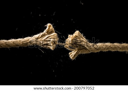 Concept of danger and risk with two ends of a frayed worn rope held together by the last strand on the point of snapping, against a dark background with copyspace. - stock photo