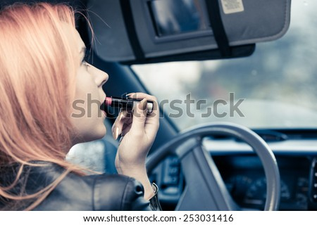 Concept of danger driving. Young woman driver red haired teenage girl painting her lips doing applying make up while driving the car. - stock photo