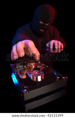 Concept of data theft with hooded thief stealing computer information stored in hard drive - stock photo
