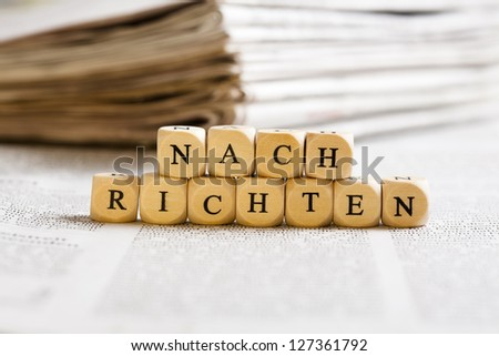 Concept of dices with letters forming word: Nachrichten (German for News). Generic newspaper background with some blurred text on the bottom and paper stack in the back.
