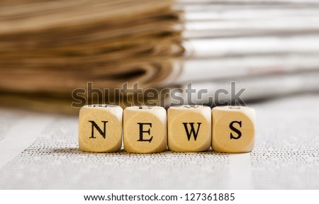 Concept of dices with letters forming word: News. Generic newspaper background with some blurred text on the bottom and paper stack in the back. Dices made from wood with natural imperfections.