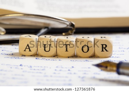 "Concept of dices with letters forming words: Autor (German version of ""author""). Generic handwritten text, pen, glasses and books as background.  Dices made from wood with natural imperfections - stock photo"