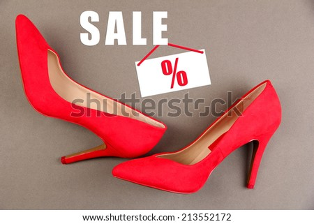 Concept of discount. Beautiful red female shoes, on grey background - stock photo