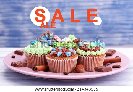 Concept of discount. Tasty cupcakes with butter cream, on plate, on color wooden background - stock photo