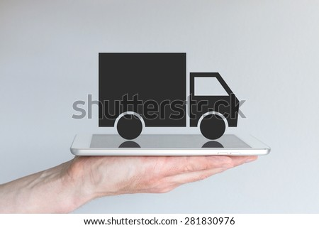 Concept of disruptive digital transportation / logistics business model. Hand holding tablet or large smart phone in front of grey background. Symbol of a simplified black truck. - stock photo