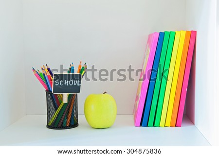 Concept of education. A yellow apple, pencils in holder and multi colored books on the light-coloured bookshelf with copy-space - stock photo