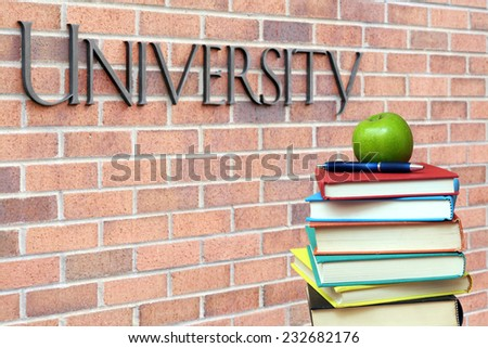 concept of education: books and apple in the front of university  - stock photo