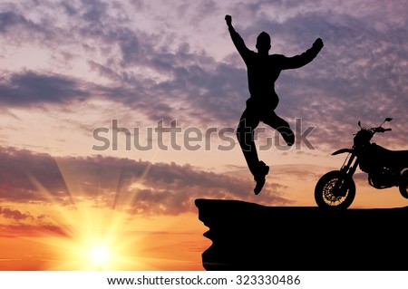 Concept of emotion. Silhouette of a man jumping on the background of motorcycle and sunset - stock photo