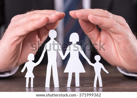 Concept of family insurance with hands protecting a family - stock photo