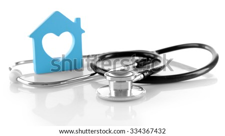 Concept of family medicine - blue plastic house with heart shaped window and stethoscope isolated on white background - stock photo