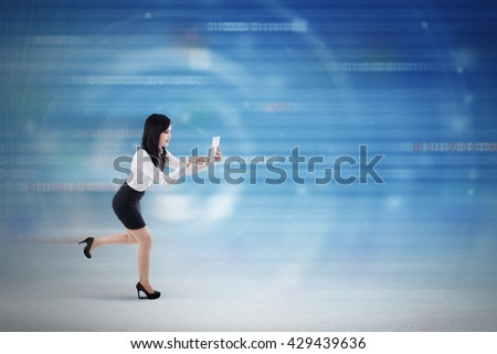 Concept of fast internet connection with a young businesswoman running inside cyberspace while using a digital tablet - stock photo
