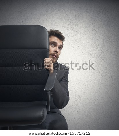 Concept of fear of a businessman behind a chair - stock photo