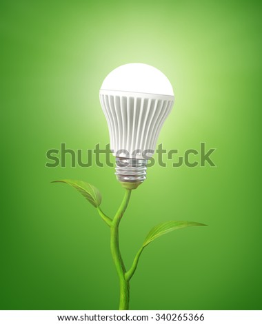 Concept of green energy. The LED light bulb illuminated on stem of plant on a green background. - stock photo