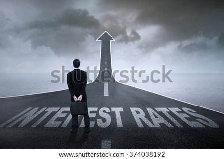 Concept of growing interest rates. Entrepreneur standing on the highway with Interest Rates text on it - stock photo