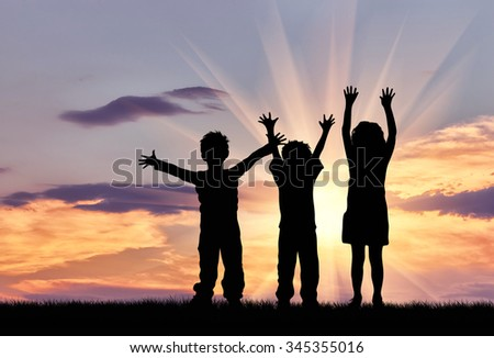 Concept of happiness. Silhouette of happy children on a sunset background