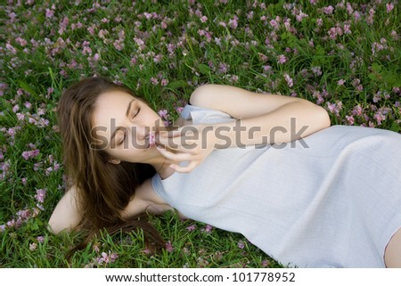 concept of harmony. Beautiful girl lying on green grass with flowers and holding a flower - stock photo