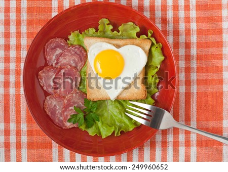 Concept of healthy breakfast - fried heart-shaped egg on toast with salad and sausage for Valentines Day or Easter - stock photo