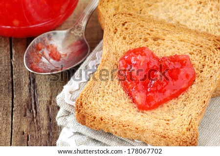 Concept of healthy breakfast - slices of wholewheat toast with red-orange marmalade spread in the shape of heart. - stock photo