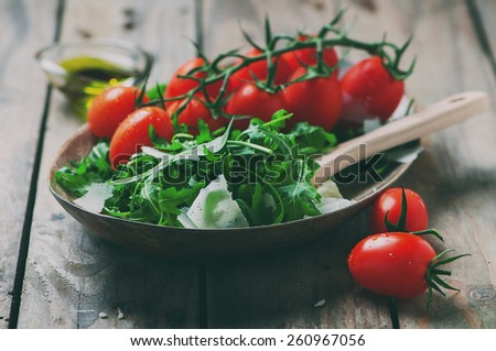 Concept of healthy italian food with arugula, tomato and cheese, selective focus and toned image