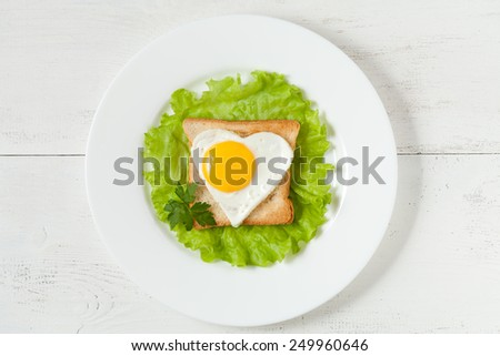 Concept of healthy, super food breakfast or lunch - slice of wholewheat toast with fried heart-shaped egg, salad and parsley for valentines day or easter - stock photo