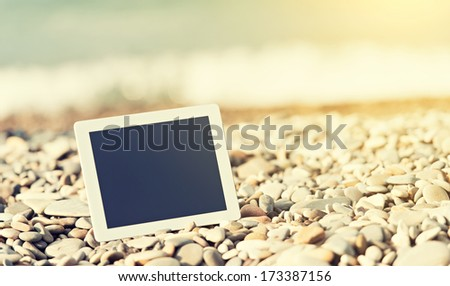 concept of internet and communication. blank empty tablet computer on the beach - stock photo