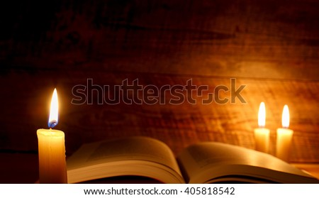 concept of knowledge, vintage book with candle