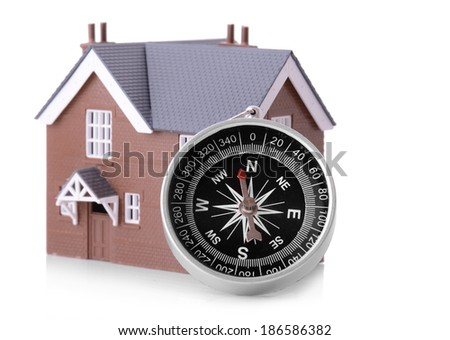 Concept of looking for a house, a compass with small house isolated on a whits background - stock photo