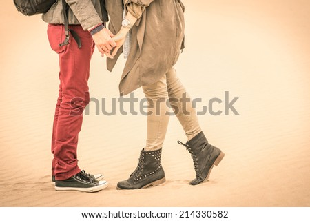 Concept of love in autumn - Couple of young lovers kissing outdoors with closeup on legs and shoes - Desaturated nostalgic filtered look - stock photo