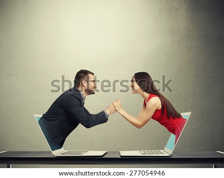 concept of love in social network. young man got out of the computer and holding hand of beautiful young woman who got out of another computer over dark background - stock photo
